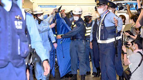 Muncitorii de salvare poartă o targă, despre care se crede că transportă un pasager rănit la stația Sushigaya Okura după ce a fost înjunghiat pe un tren de navetiști, la Tokyo, vineri seară.