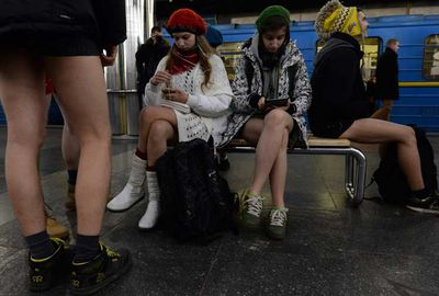 Commuters behave as usual, except without pants.