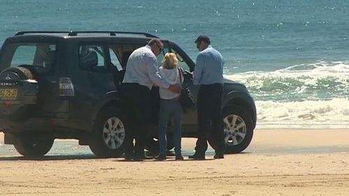 A woman is comforted at the scene of a fatal shark attack at Byron Bay. (9NEWS)