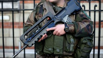 A French soldier stands guard outside a Jewish school in Paris following recent terror attacks. (AAP)