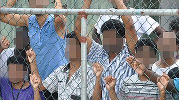 Refugees at Manus Island peer through a security fence. (AAP)
