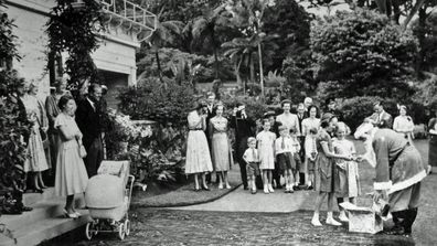 The Queen and Duke of Edinburgh stand on the steps of Government House, Auckland, New Zealand, on Christmas Day. Father Christmas gives presents to the Governor General's two young daughters. (Photo: 25 December, 1953)