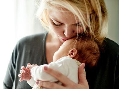 Mum kissing newborn baby