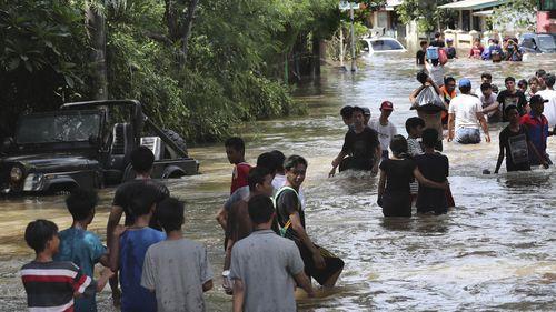 People wade through a flooded neighbourhood in Tanggerang outside Jakarta, Indonesia, Thursday, Jan. 2, 2020.