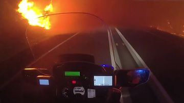 A Queensland Police motorbike travels through the fire.
