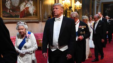 The Queen and Donald Trump enter the royal banquet.