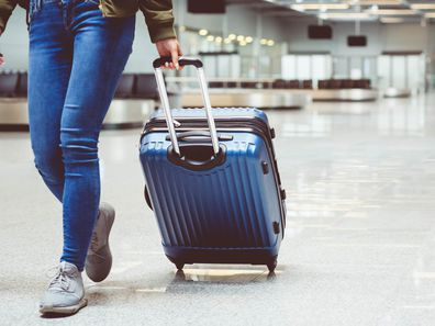 Woman in international airport walking with luggage