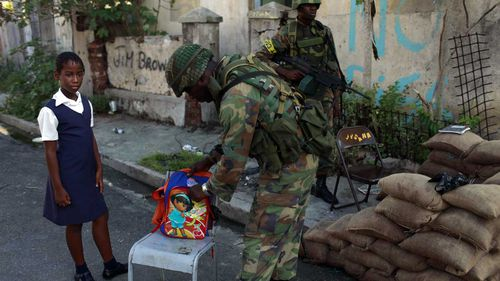 A soldier checks the backpack of a schoolgirl in Kingston, Jamaica. (AAP)