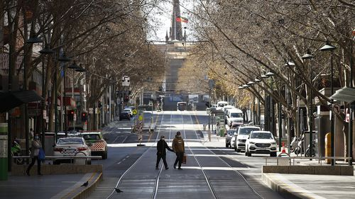 A woman is seen exercising along a quiet Bourke Street on September 06, 2020 in Melbourne, Australia.
