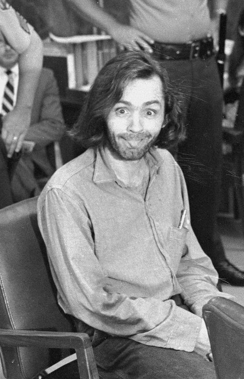 Charles Manson sticks his tongue out at photographers as he appears in a Santa Monica courtroom on June 25, 1970. (AP Photo)