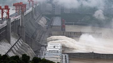 In this photo released by China's Xinhua News Agency, water flows out from sluiceways at the Three Gorges Dam on the Yangtze River near Yichang in central China's Hubei Province, Friday, July 17, 2020.