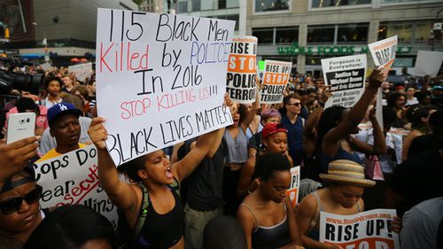 People hold banners and chant slogans as they march from Union Square Park to Grand Central to protest the killing of 3 black men by police in 48 hours