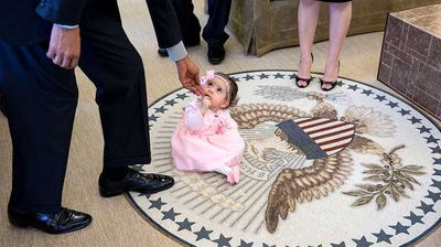 Six-month-old Sabina Johnson takes a seat on the Seal of the Presidency. (Flickr/White House)