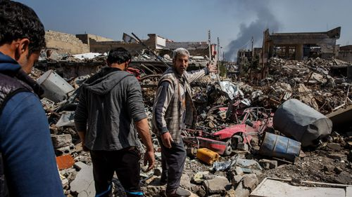 Residents in Mosul wade through rubble after a coalition air strike in 2017.