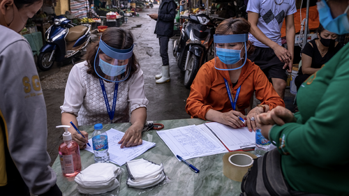 HANOI, VIETNAM - APRIL 18: Market staff wear face shields while taking information from vendors and labourers at Long Bien market for coronavirus disease (COVID-19) rapid test on April 18, 2020 in Hanoi, Vietnam.