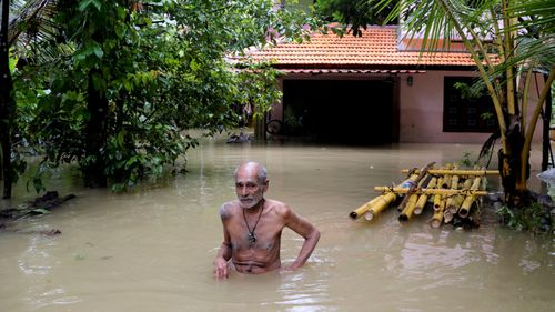 An elderly man wades through flood waters to reach a boat carrying food supplies for stranded people in Chengannur in the southern state of Kerala, India.
