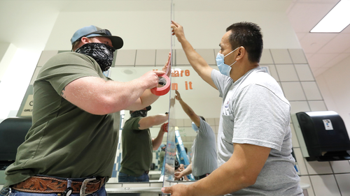 Wearing mask amid the concern of COVID-19, Richardson Independent School District workers Rogelio Ponciano, right, and Matt Attaway install a plexiglass barrier on the sink in the restroom for students at Bukhair Elementary School in Dallas, Wednesday, July 15, 2020. (AP Photo/LM Otero)