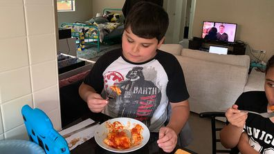 Giovanni with autism eating lasagne.