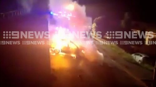 The car slammed into a power pole, causing it to split and catch fire. (9NEWS)