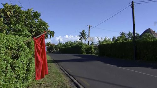 Red flags are hung outside homes where families are not vaccinated.