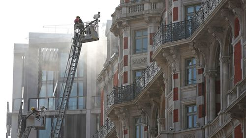 Fire crews try to extinguish the fire which started on the roof. (AAP)