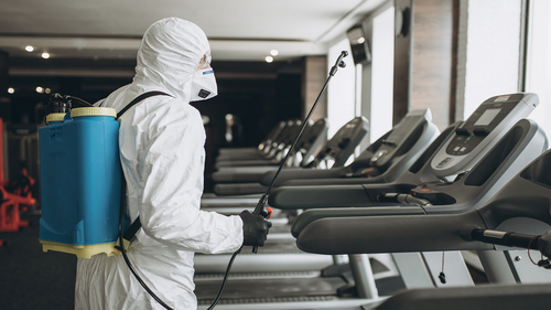 A worker in a protective suit cleans exercise equipment. The Centres for Disease Control, on Monday, April 19, 2021, said the risk of surface transmission of COVID-19 is low.