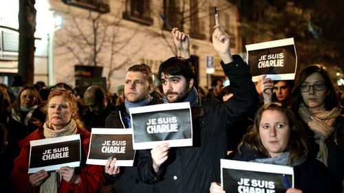Demonstrators hold pencils during a rally outside France's embassy in Madrid, Spain in solidarity with the slain Charlie Hebdo employees. (AAP)