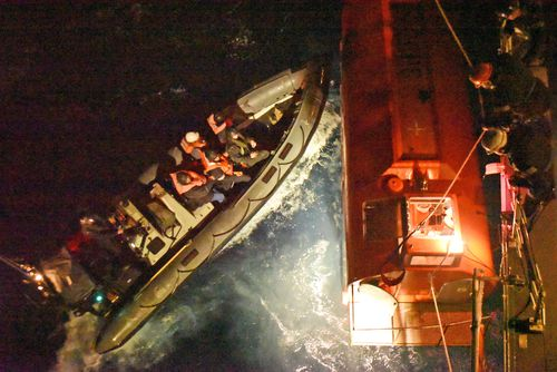 Britain's HMS Argyll aboard an inflatable boat nudge the lifeboat of Grande America, towards HMS Argyll as other crew members secure the lifeboat, Monday March 11, 2019. The crew of HMS Argyll spent eight hours saving all 27 crew from the Italian registered 28,000-tonne merchant ship Grande America.