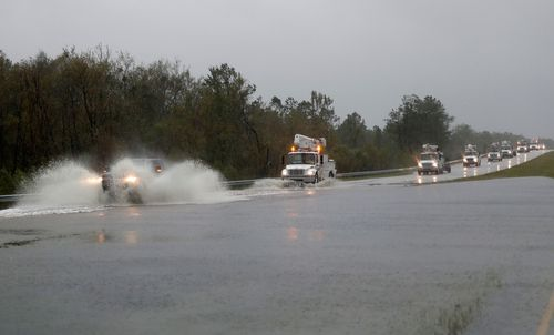 Power company trucks make their way through water on highway US 17 near Jacksonville, North Carolina.