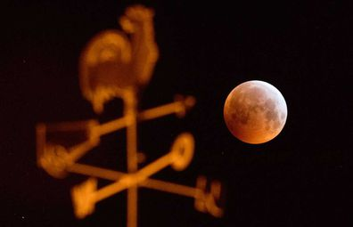 """21 January 2019, Lower Saxony, Laatzen: Darkened, the full moon appears as a so-called """"blood moon"""" and appears reddish - photographed behind a weathercock on the roof of a house. Moon, sun and earth are exactly in one line during a lunar eclipse."""
