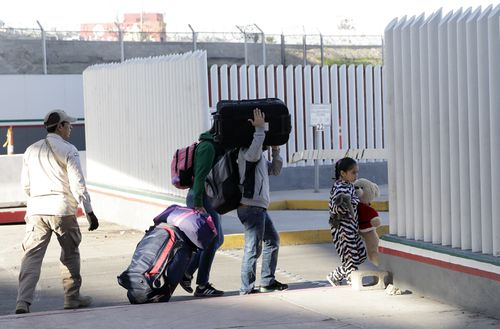 A family leaves to apply for asylum in the United States, at the border.