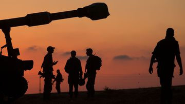 Israeli soldiers prepare their artillery unit near the border with Gaza Strip.