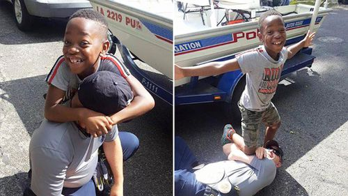 Boy poses with police officer who saved his wrestling belt from Louisiana floodwaters