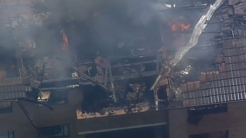 The fire spread to the roof of the unit block in Merrylands.