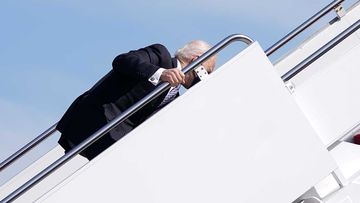Joe Biden finds his feet after slipping on the steps up to Air Force One.