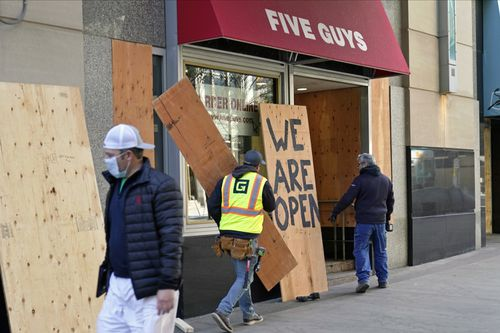 A passerby walks past workers boarding up a Five Guys restaurant along the Nicollet Mall Monday, Nov. 2, 2020, in Minneapolis ahead of the contentious presidential election on Tuesday. Many businesses along the popular downtown mall have been boarded up following unrest that followed the death of George Floyd at the hands of Minneapolis police on Memorial Day. (AP Photo/Jim Mone)