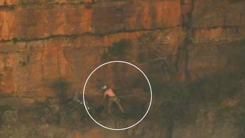 An injured rock climber hangs off a Blue Mountains cliff, waiting to be winched to safety by a rescue helicopter.