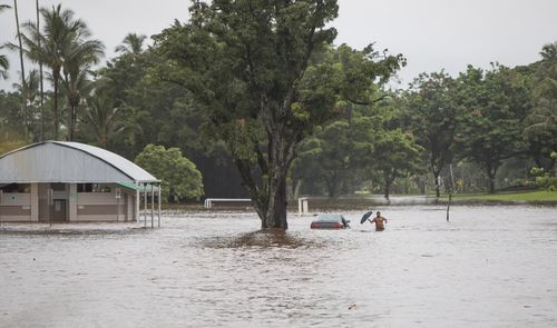 One man has forded floodwaters in an attempt to recover possessions from his car.