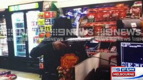 A man who was caught on CCTV camera pointing a shotgun in the face of a Melbourne shop employee has been arrested. Picture: 9NEWS.