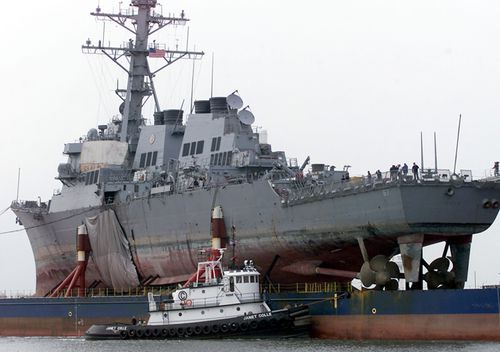 The tugboat Janet Colle assists the USS Cole as it is returned back to the United States December 13, 2000 at Ingalls Shipbuilding in Pascagoula, MS. (Getty)