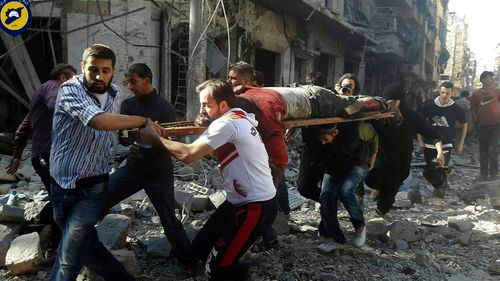 Syrians carry a victim after airstrikes by government helicopters on the rebel-held Aleppo neighbourhood of Mashhad. (AAP)