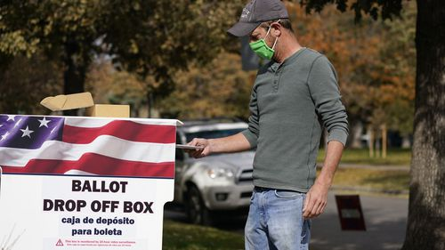 A voter wears a face covering as he place a ballot in a drop box outside the La Familia Recreation Center, south of Denver.