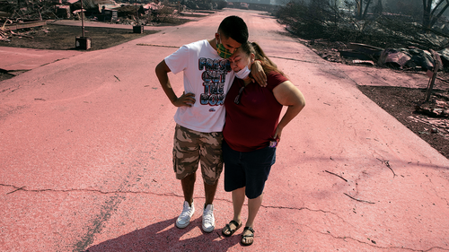 Maria Centeno from Mexico, is consoled by her son, Hector Rocha after seeing their destroyed mobile home at the Talent Mobile Estates as wild fires devastate the region on Thursday in Talent, Ore.  (AP Photo/Paula Bronstein)