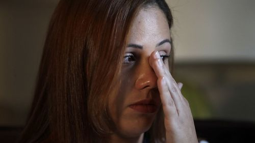 Lidia Karine Souza, who is seeking asylum from Brazil, wipes a tear as she talks about the ordeal she has lived in searching for and finally seeing her son. (AP)