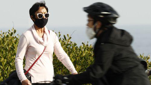 A woman, wearing a face mask, walks along St Kilda on July 25, 2020 in Melbourne, Australia.