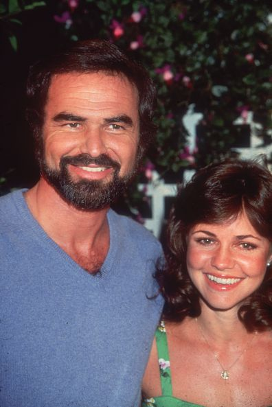 American actor Burt Reynolds smiles with his girlfriend, actor Sally Field, while attending an outdoor event. He wears a blue V-neck sweater, and has a beard and mustache.