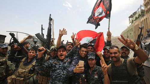 Members of the Iraqi federal police dance and wave their country's national flag as their part of the battle for the Old City of Mosul is declared accomplished. (AFP)