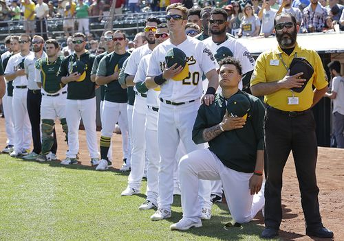 Bruce Maxwell takes a knee during the national anthem at a baseball game. (AAP)