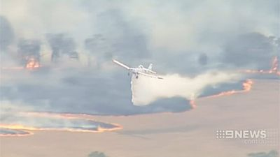 A firefighting plane dumps a load of water on a grassfire burning near Ararat in Victoria. (9NEWS)
