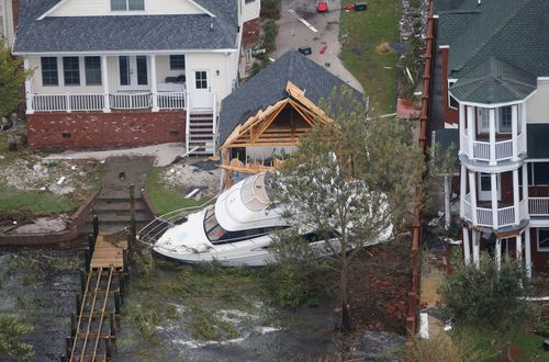 A yacht sits on the Neuse river bank in between buildings after hurricane Florence passed through the area in New Bern, North Carolina.